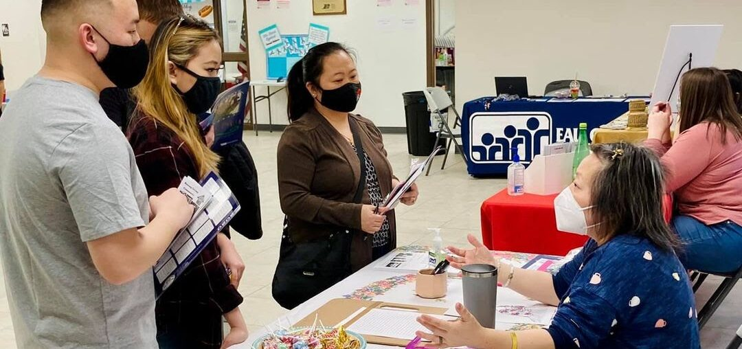 Hmong PTA President Caitlin Lee speaks with an Eau Claire family about Hmong resources.