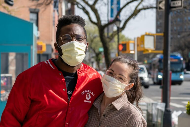 Man and woman, wearing masks, standing in busy city sidewalk, looking at camera